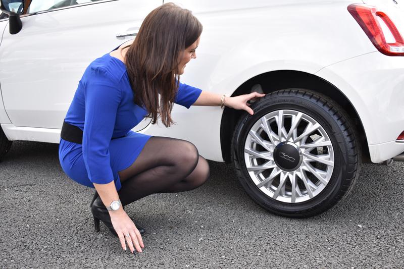 Marie vérifie la pression et l'usure des pneus de sa Fiat 500 achetée chez VPN Autos.